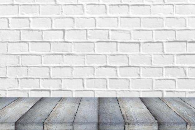 Estante de madera o mesa delante de un fondo de pared de ladrillo blanco limpio y vacío con espacio para texto o ideas