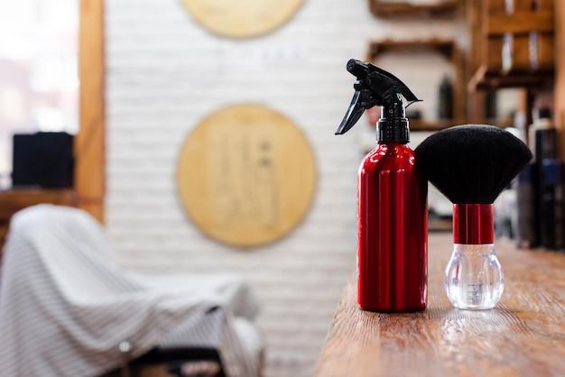 Estante de madera con pincel rojo y pulverizador.