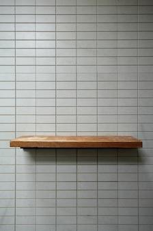 Estante de madera vacío en la pared de azulejos.