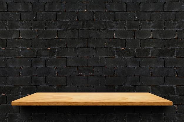 Estante de madera vacío del tablero en el fondo negro de la pared de ladrillo para el producto de la exhibición