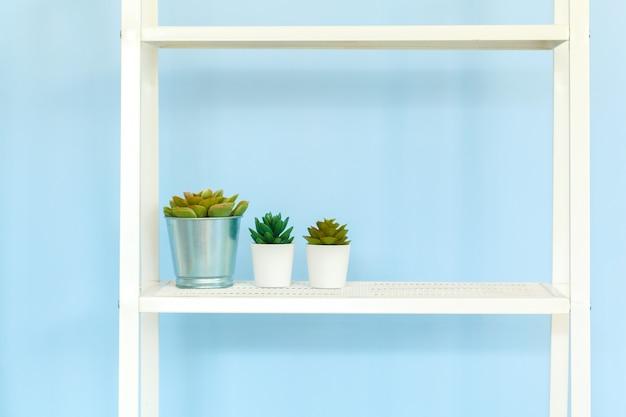 Estante de metal blanco con libros contra el fondo azul.