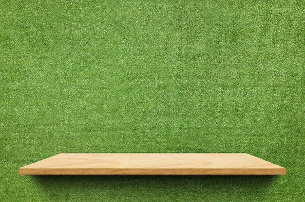 Estante de tablero de madera vacío en el falso fondo de pared de hierba verde
