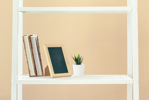Estantería blanca con libros y papelería contra la pared beige