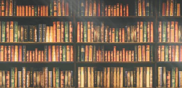 Estantería borrosa muchos libros antiguos en una librería o biblioteca.
