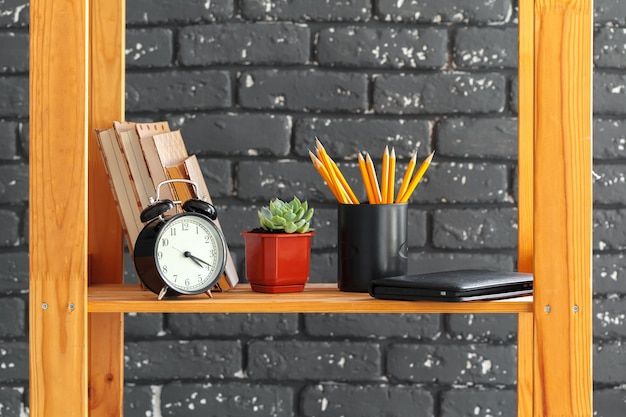 Estantería de madera con libros y cosas contra la pared de ladrillo negro