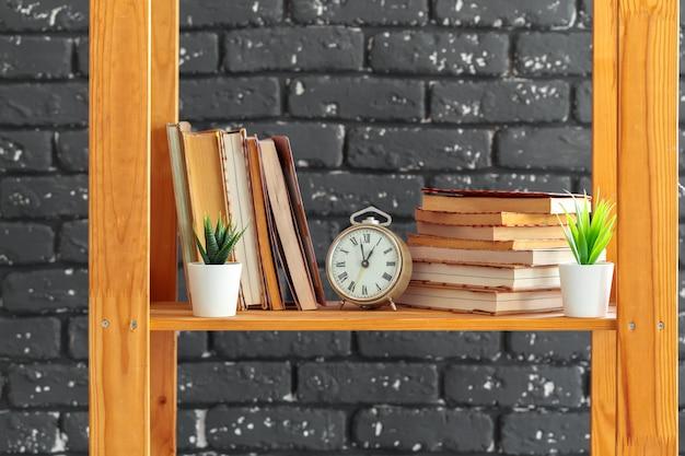 Estantería de madera con libros y cosas contra la pared de ladrillo negro.