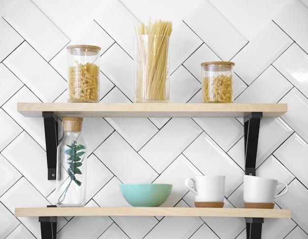 Estantes de cocina de madera con vasos y tarros de cristal.