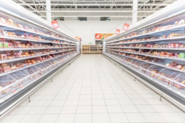 Estantes con comida fría en un supermercado. espacio para texto. borroso.
