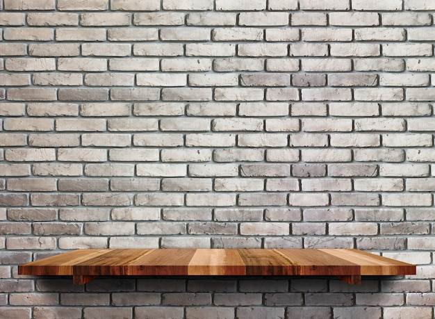 Estantes de madera vacíos en la pared de ladrillo negro.