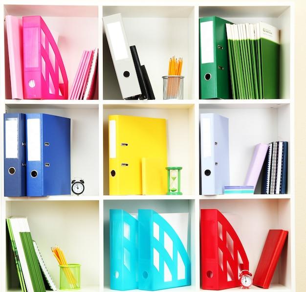 Estantes de oficina blancos con diferentes artículos de papelería, cerrar