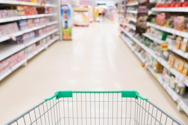 Estantes de productos de pasillo de supermercado con carrito de compras verde vacío desenfocado fondo del cliente