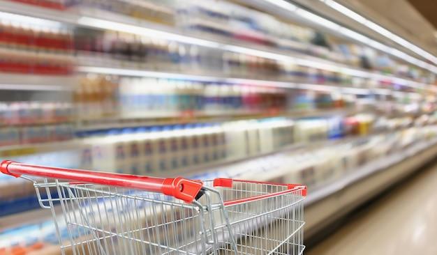 Los estantes de la tienda de comestibles del supermercado con el carro de compras rojo vacío