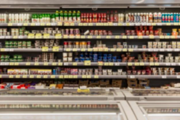 Estantes con variedad de productos lácteos en el supermercado. borroso. vista frontal.