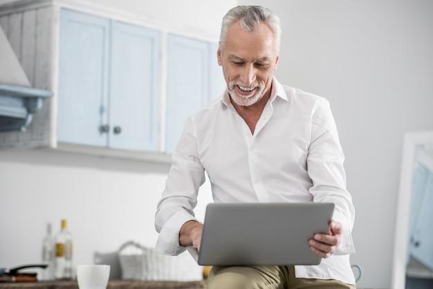 Estar contento. hombre maduro feliz manteniendo una sonrisa en su rostro y sosteniendo la computadora portátil mientras lee el mensaje