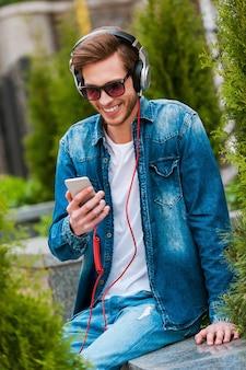 Estar en mi propia ola. feliz joven en auriculares sosteniendo teléfono móvil y sonriendo