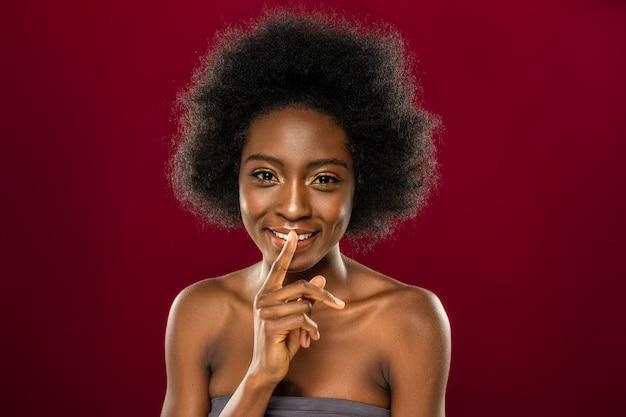Estar en silencio. encantado de mujer agradable sosteniendo su dedo cerca de los labios mientras está en silencio