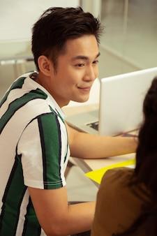 Estar en todos los oídos. hombre asiático alegre manteniendo una sonrisa en su rostro mientras escucha a su tutor