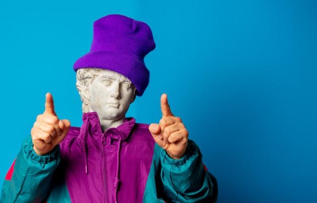 Una estatua antigua vestida con ropa de moda de los noventa te señala