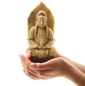 Estatua de buda celebrada en mano sobre blanco