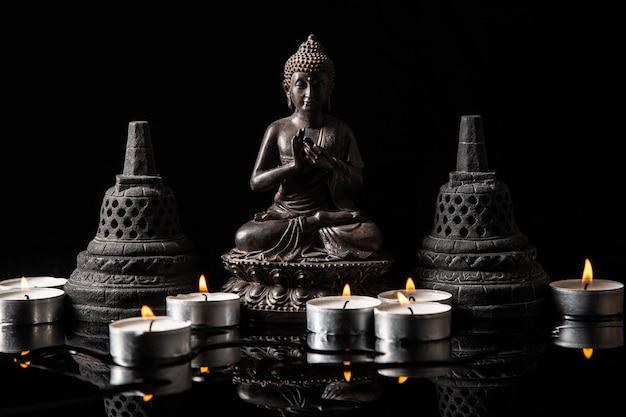 Estatua de buda sentado en meditación, con velas y campanas budistas.