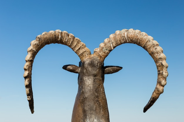 Estatua de cabra con cuernos con cielo azul