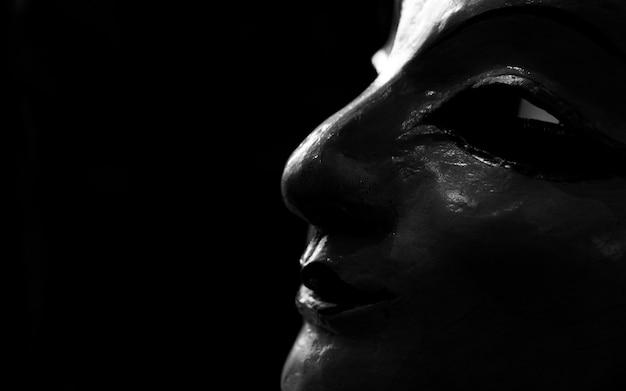 Estatua cara de mujer hecha de yeso. cara de estatua de mujer sobre fondo oscuro. escultura de arte. estatua cara de mujer buscando algo.
