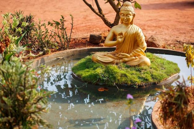 Estatua dorada de buda junto al estanque en goa