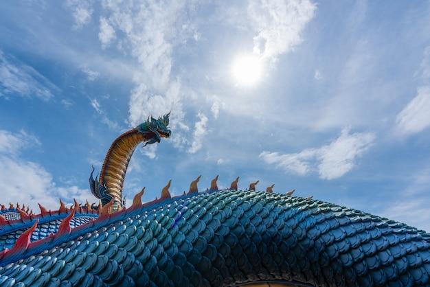 Estatua del gigante naga tailandés estatua con nubes de cielo azul en el templo de phu manorom en mukdahan provinc
