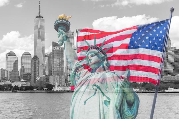 Estatua de la libertad con una gran bandera americana y el horizonte de nueva york en el