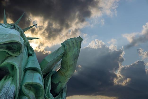 Estatua de la libertad con el hermoso cielo anaranjado colorido atardecer en manhattan, ciudad de nueva york, ee.