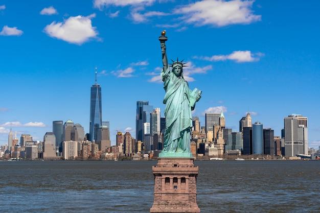 La estatua de la libertad sobre la escena del lado del río del paisaje urbano de nueva york, cuya ubicación es más baja en manhattan