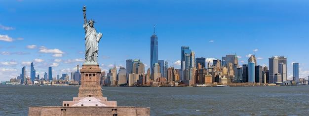 La estatua de la libertad sobre la escena panorámica del paisaje urbano de nueva york junto al río, cuya ubicación es manhattan, estados unidos de américa, estados unidos, arquitectura y edificio turístico