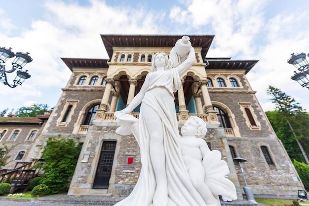 Estatua de mármol frente a la entrada del castillo de cantacuzino en busteni