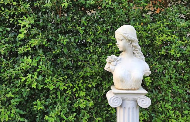 Estatua de la mujer en el jardín con el espacio de la copia. hoja de pared en parque natural.