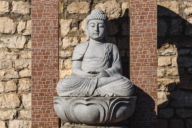 Estatua de piedra blanca de un buda en mesa de mampostería
