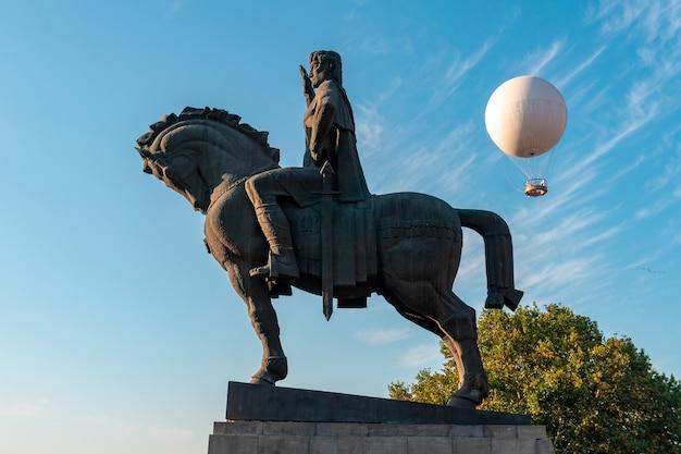Estatua del rey vakhtang gorgasali en tbilisi, excursión en globo para pasajeros contra el cielo azul de tbilisi, georgia.