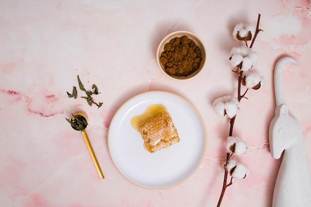 Estatua de unicornio; granos de café; hojas; ramita de capullo de algodón con nido de abeja en cerámica sobre fondo texturizado rosa