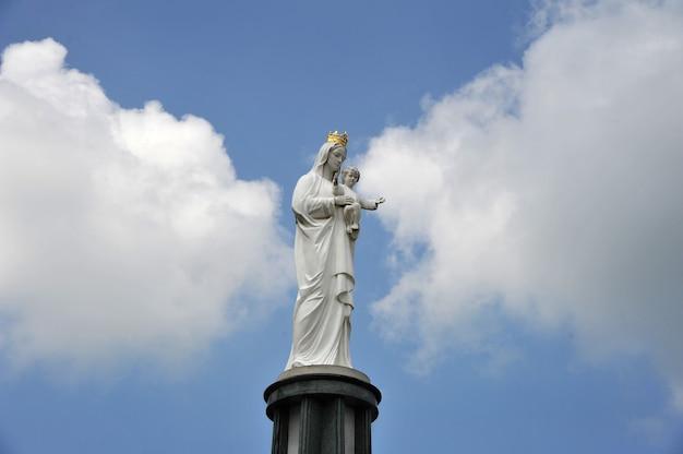 Estatua de la virgen maría con el pequeño jesús en las manos.
