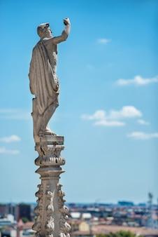 Estatuas de mármol blanco en el techo de la famosa catedral duomo di milano en la piazza de milán, italia