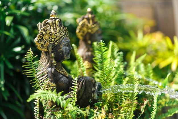 Estatuilla balinesa de una diosa con una olla de la que fluye el agua. decoración de la piscina