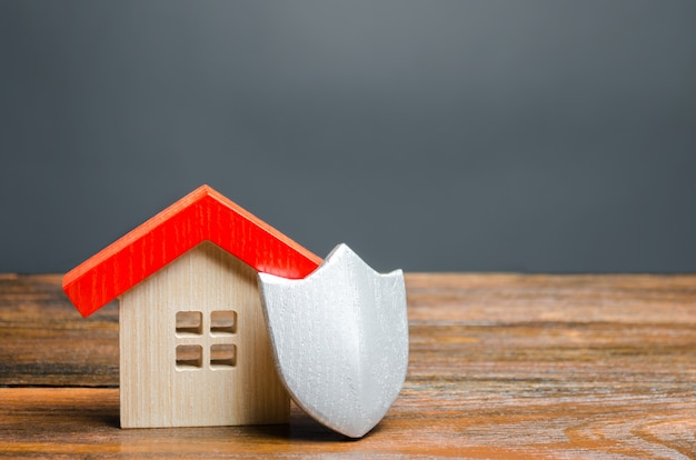 Estatuilla de casa y escudo protector. el concepto de seguridad del hogar y la seguridad. sistemas de alarma
