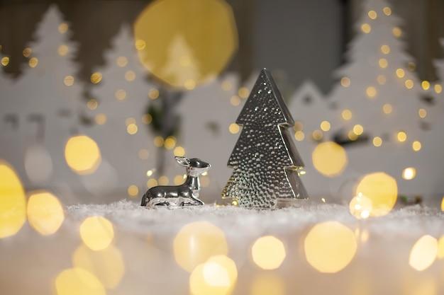 Estatuilla de un ciervo acostado cerca de un árbol de navidad