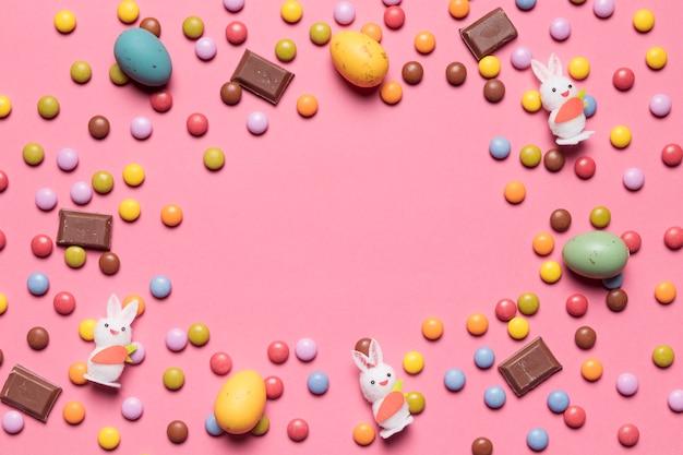 Estatuilla de conejito; caramelos de gema; huevos de pascua de chocolate con espacio en el centro sobre fondo rosa