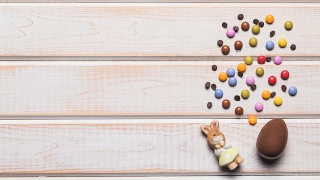 Estatuilla de conejo; huevo de pascua; caramelos de gemas con chips de chocolate en el escritorio de madera