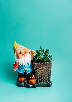 Estatuilla enana con planta de exhibición en la canasta con fondo coloreado