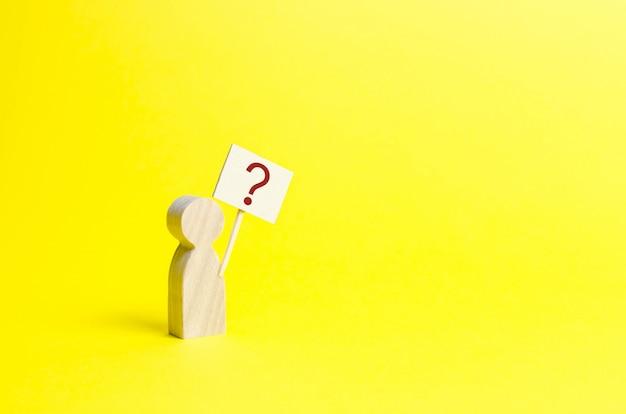 Estatuilla humana de madera con un signo de interrogación.