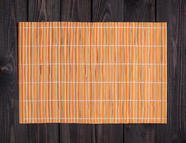 Estera de bambú en la mesa de madera, vista superior