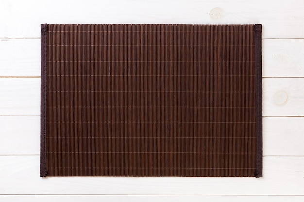 Estera de bambú oscuro sobre fondo blanco de madera