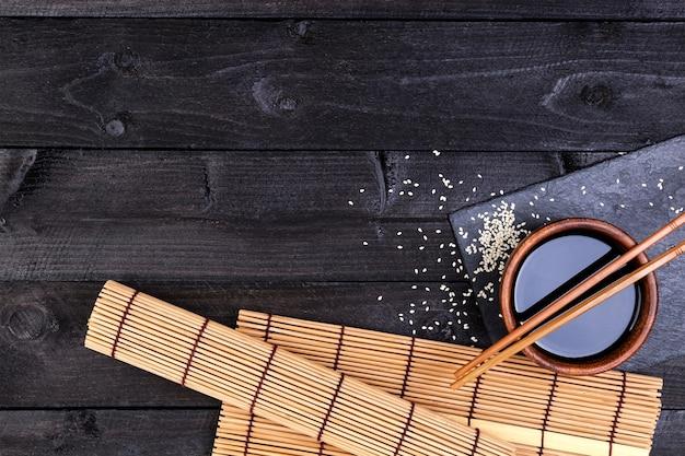 Estera de bambú, salsa de soja, palillos en la mesa oscura.