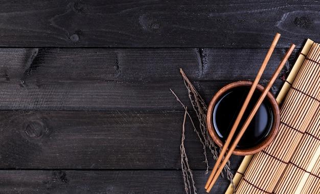 Estera de bambú, salsa de soja y palillos en la mesa oscura